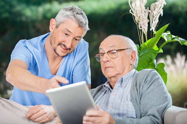 Male nurse showing something to senior man on digital tablet at nursing home porch